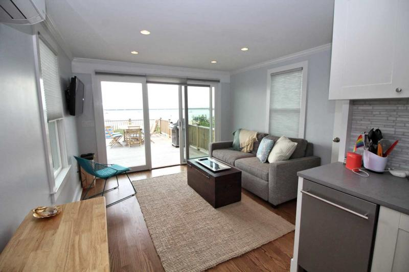Living room opens to large deck overlooking harbor