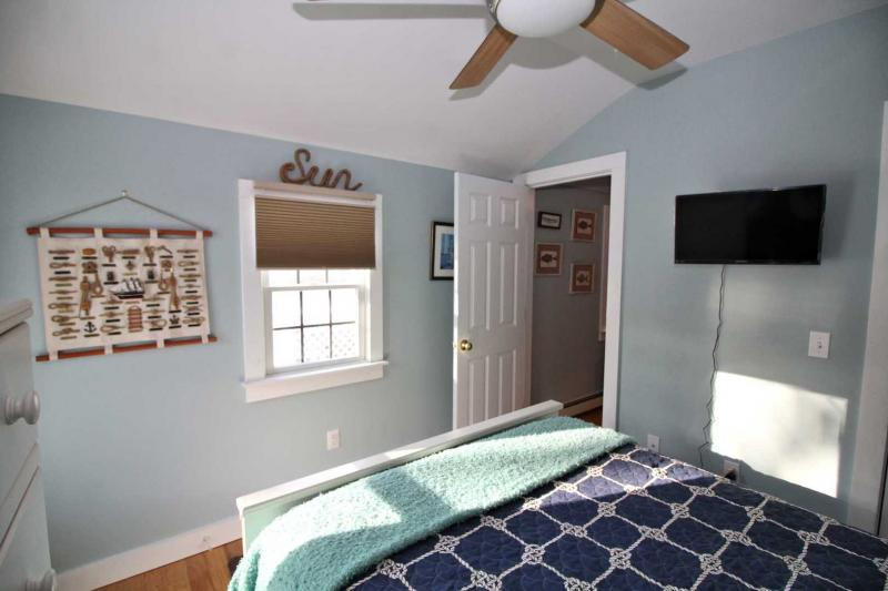 Bedroom has a television and ceiling fan
