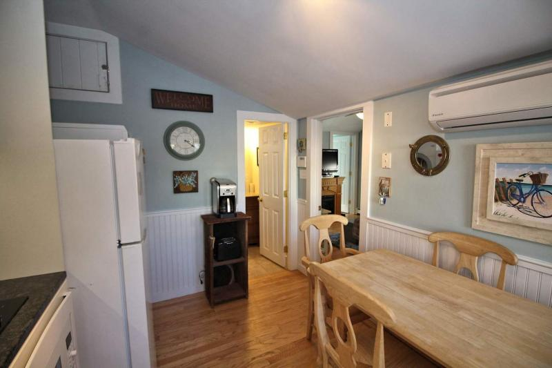 Kitchen has a ductless split unit AC and dining table