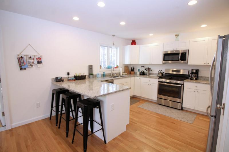 Kitchen has stainless appliances and counter seating