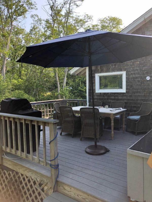 Deck off kitchen with outdoor furniture and gas grill