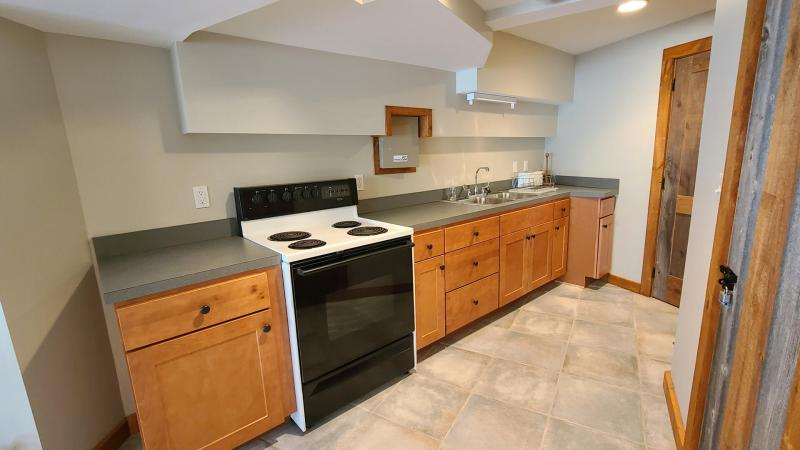 Kitchen with stove and refrigerator in rec room
