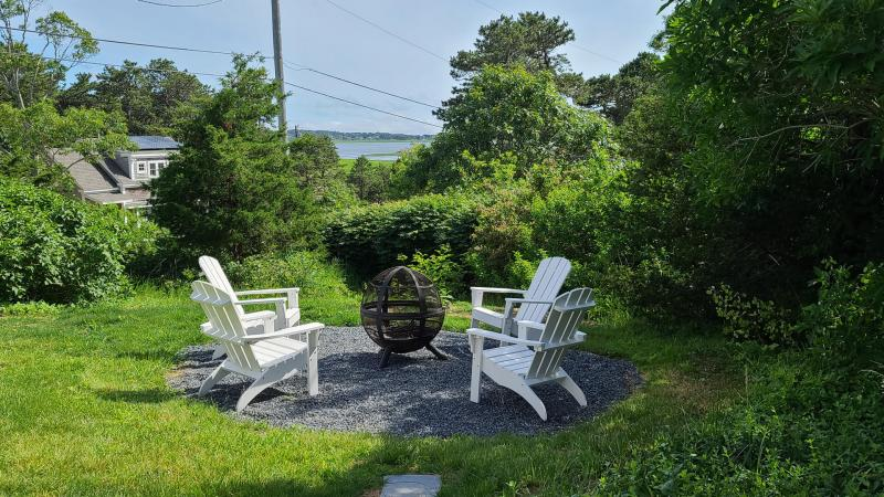 Fire pit with Adirondack chairs looks out over Wellfleet Harbor