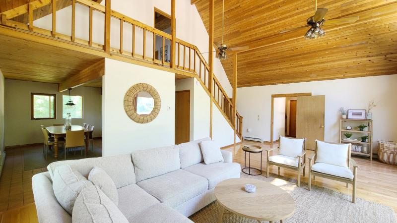 Living room has vaulted ceiling and ceiling fans