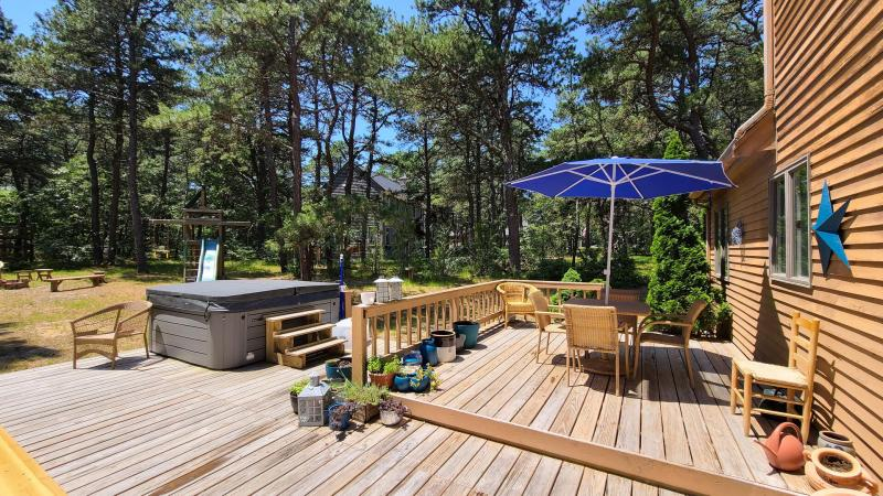 Large deck with jacuzzi and outdoor dining tables