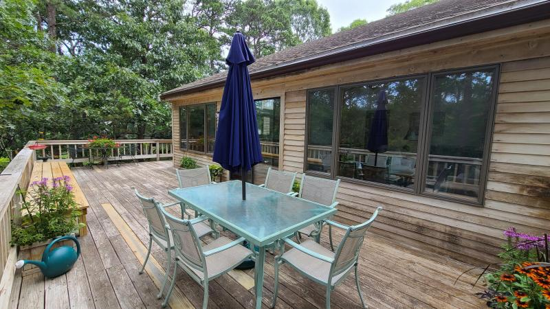 Large deck with dining table and gas grill