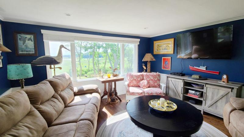 Living room has comfortable seating and a large flat screen TV