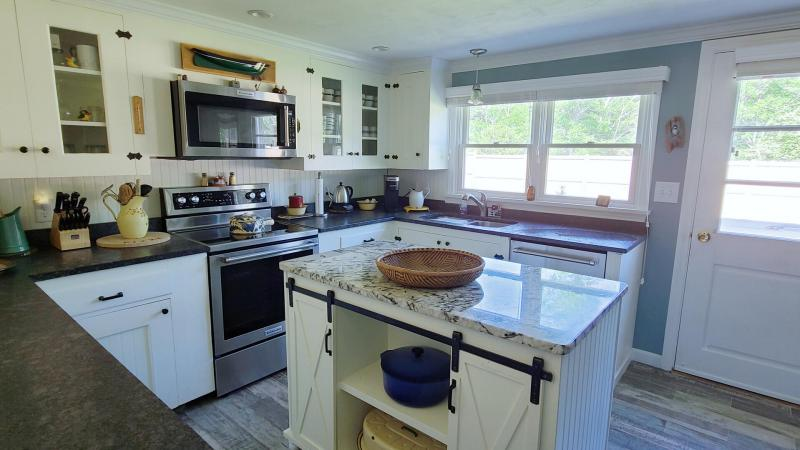 Well equipped kitchen with island and granite counter tops