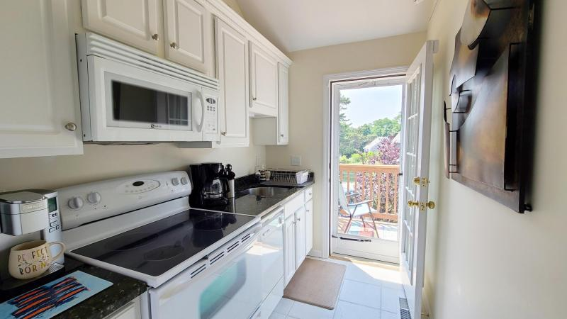 Nicely equipped galley kitchen with door to small deck