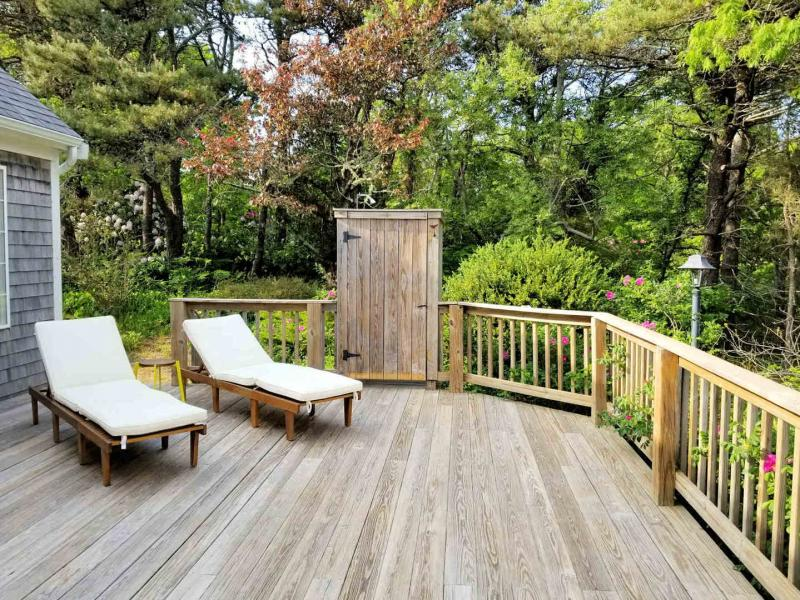 Large deck with outdoor shower and wooded view