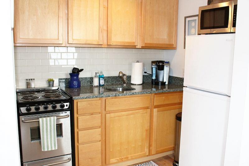 Kitchen with range and refrigerator