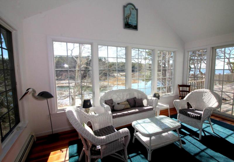 Bright sun room connects TV room and deck