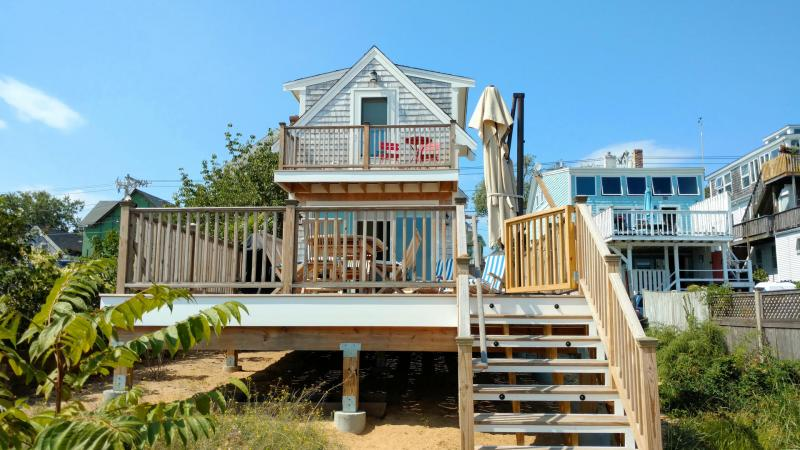 Stair from the large deck lead right to the sandy beach
