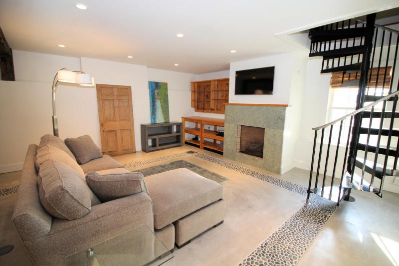 Guest house living area has flat screen TV and gas fireplace
