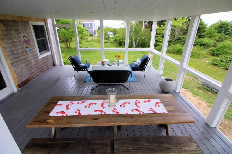 Screen porch has picnic table and outdoor furniture