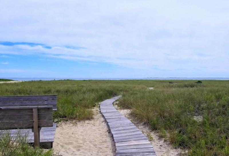 Boardwalk from property leads to sandy path to beach
