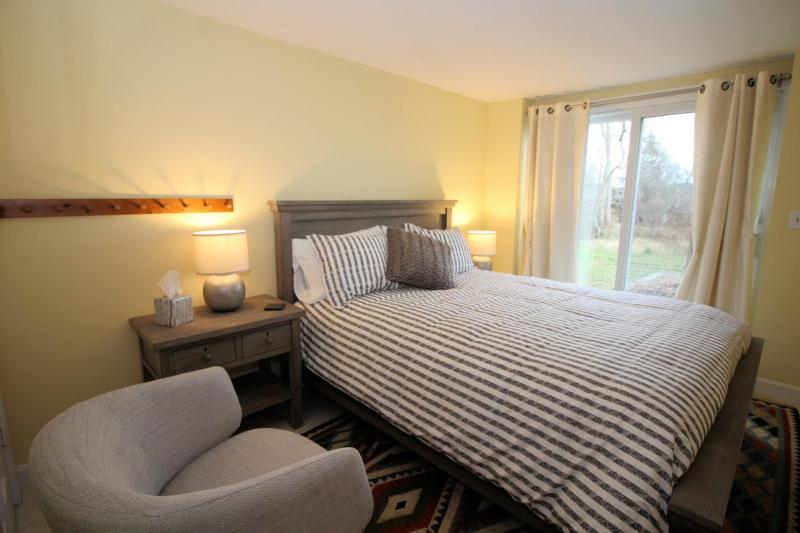 Lower level bedroom with queen bed and slider