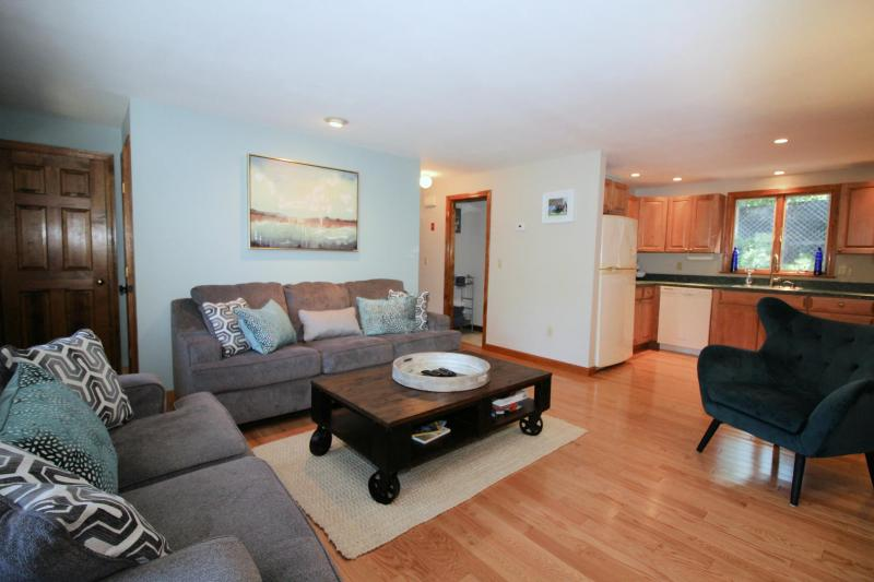 Living room has comfortable seating and  a flat screen TV with R