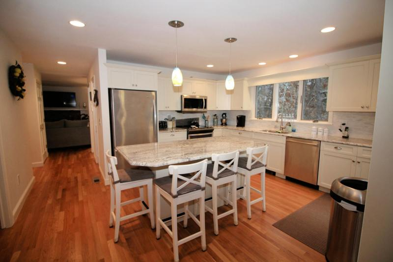 Kitchen has island with breakfast bar