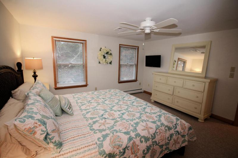 King bedroom has a TV with cable and a ceiling fan