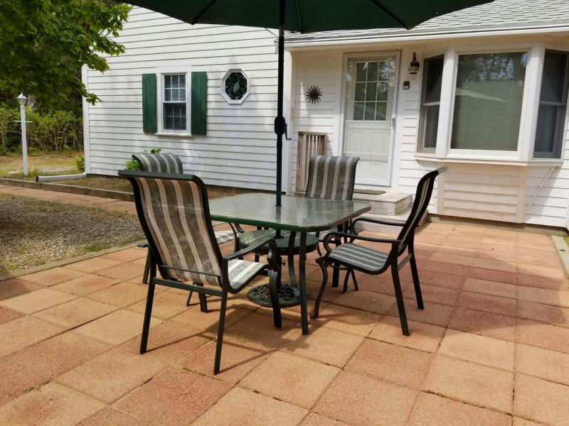 Outdoor table and chairs with grill on the patio