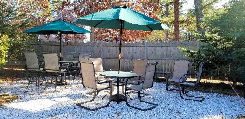 Outdoor dining area with tables and gas grill