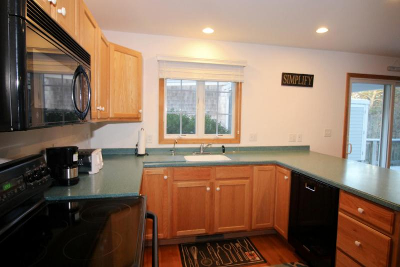 Nicely equipped kitchen with slider to deck beyond
