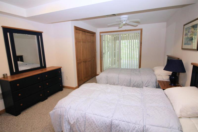 Lower level bedroom with two twins and slider