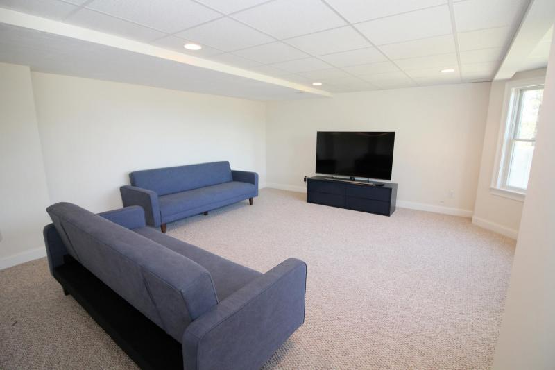 Spacious lower level family room with futons