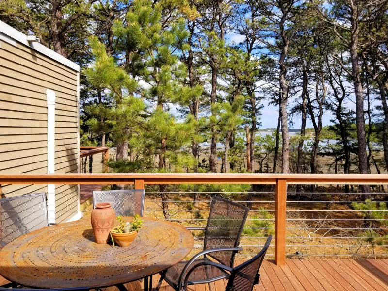 Deck with views has an outdoor table and gas grill