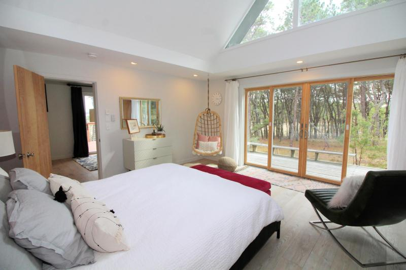 Master bedroom with slider to deck and wooded view
