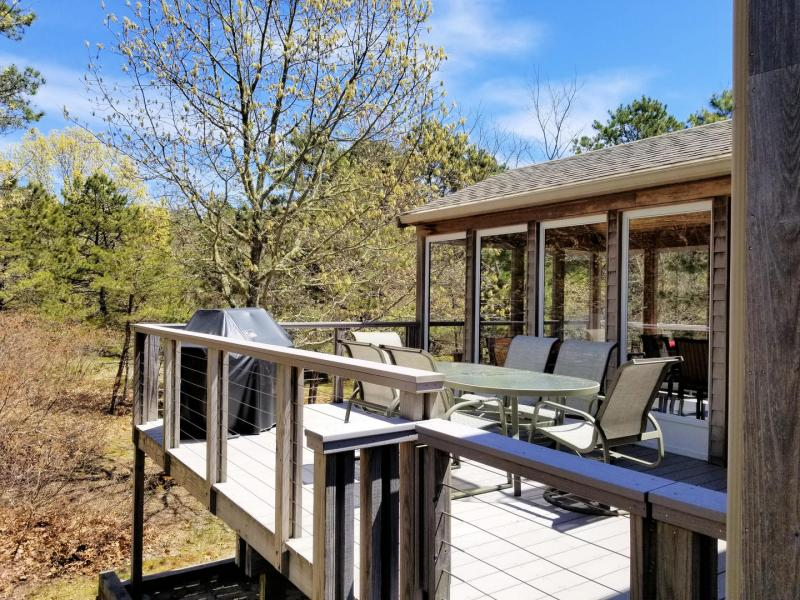 Deck with screened porch beyond both look out over backyard