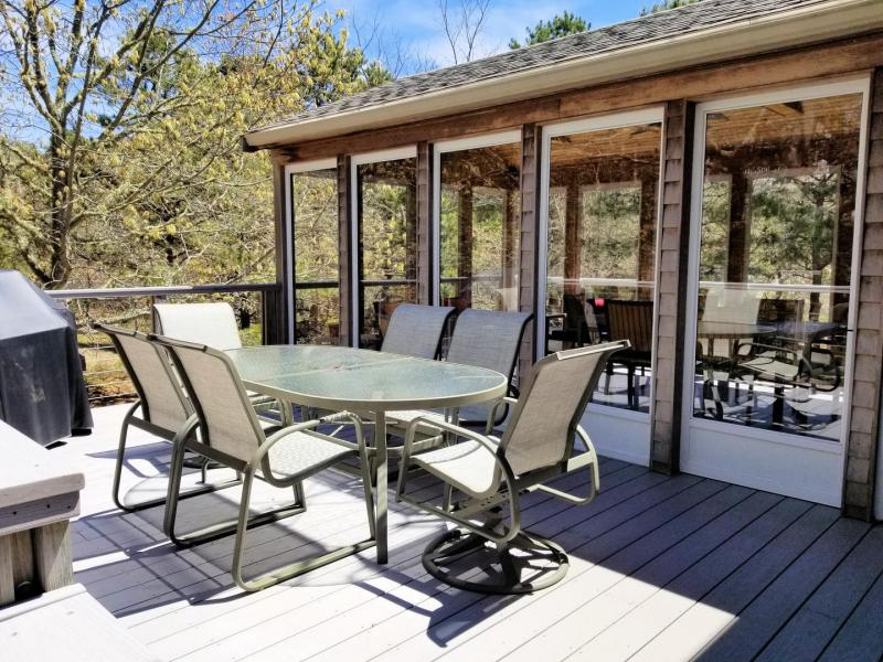 Deck has outdoor table and chairs and a gas grill