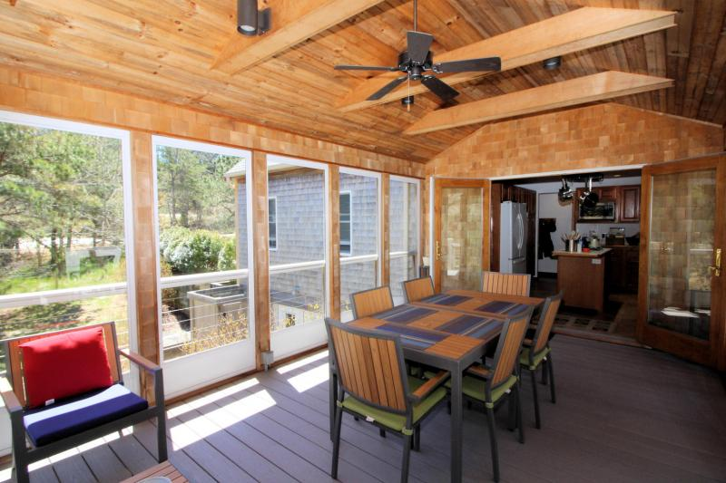 Screened porch has dining and lounging furniture