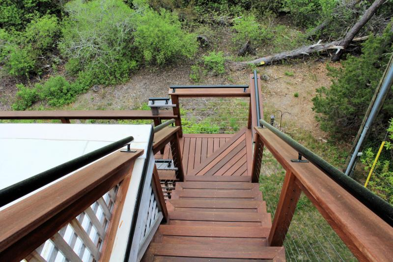 Stairs from rooftop deck to second floor deck