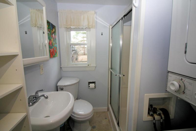 Bathroom has a shower and stacked washer and dryer