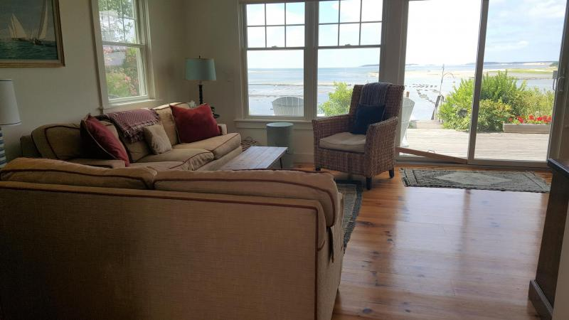 Living room looks out over deck and bay