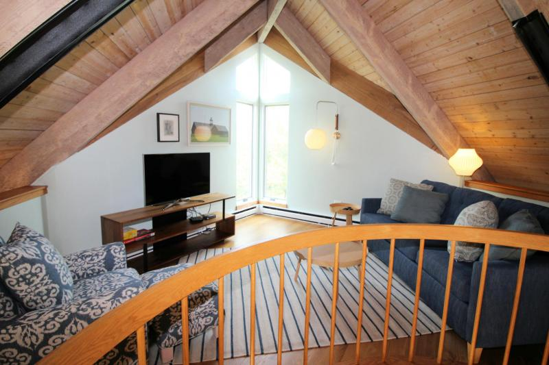 Open loft with comfortable seating and flat screen TV