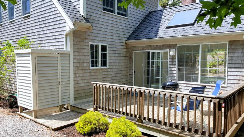 Slider from sun room leads to deck with enclosed outdoor shower